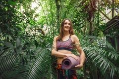 Lycklig ung kvinnlig yogainstruktör som poserar bland tropiska växter Royaltyfri Foto