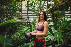 Lycklig ung kvinnlig yogainstruktör som poserar bland tropiska växter Arkivbild