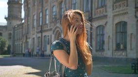 Lycklig ung ljust rödbrun kvinna som talar på telefonen och ler och att stå på gatan som bygger i bakgrund, vind i hennes hår stock video