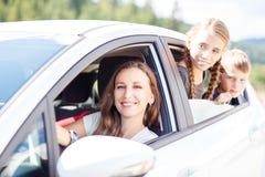 Lycklig ung mamma och hennes barn som sitter i en bil Royaltyfri Bild