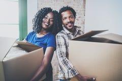 Lycklig ung man för svart afrikan och hans flickvänflyttningaskar in i nytt hus tillsammans och danande per lyckat liv royaltyfri fotografi