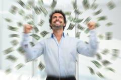 Lycklig ung man i ett regn av pengar royaltyfria bilder