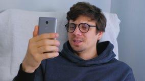Lycklig ung man i exponeringsglas som talar video pratstund p? smartphonen som sitter i f?t?ljen, online-datum arkivfilmer
