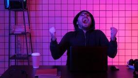 Lycklig ung man i glasögon som håller ögonen på dataspelen Emotionell reaktion arkivfoton