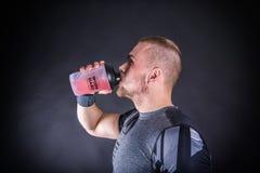 Lycklig ung man i sportswear som dricker energidrinken på idrottshallen mot mörk bacground Royaltyfri Foto