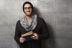 Lycklig ung man med boken arkivfoto