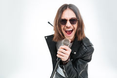Lycklig ung man med långt hår genom att använda mikrofonen för att sjunga arkivbilder