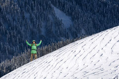 Lycklig ung man med ryggsäckanseende på snöig berglutning Alpinist- eller bergfotvandrare Arkivfoton