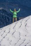 Lycklig ung man med ryggsäckanseende på snöig berglutning Alpinist- eller bergfotvandrare Arkivfoto