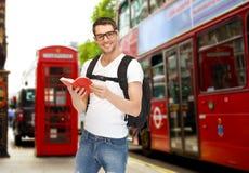 Lycklig ung man med ryggsäck- och bokresande Fotografering för Bildbyråer