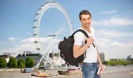 Lycklig ung man med ryggsäck- och bokresande Royaltyfri Bild
