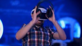 Lycklig ung man med virtuell verklighethörlurar med mikrofon med kontrollantgamepad som spelar den tävlings- videospelet Arkivfoton
