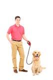 Lycklig ung man och en hund på en koppel Fotografering för Bildbyråer