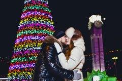 Lycklig ung man och kvinna som kysser under chimes på julhelgdagsafton arkivbilder