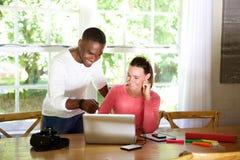Lycklig ung man och kvinna som ser bärbara datorn royaltyfri fotografi