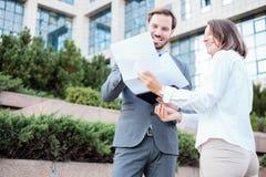 Lycklig ung man och kvinnligt affärsfolk som framme talar av en kontorsbyggnad, har ett möte och diskuterar arkivfoton