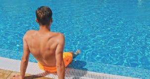 Lycklig ung man på simbassängen lager videofilmer