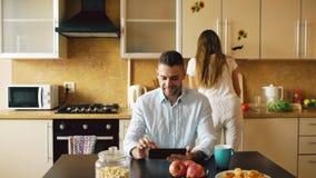 Lycklig ung man som använder digitalt minnestavladatorsammanträde i köket medan hans flickvän som hemma lagar mat royaltyfri fotografi