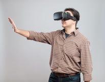 Lycklig ung man som använder virtuell verklighethörlurar med mikrofon Arkivfoto