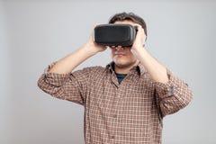 Lycklig ung man som använder virtuell verklighethörlurar med mikrofon Fotografering för Bildbyråer