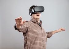 Lycklig ung man som använder virtuell verklighethörlurar med mikrofon Royaltyfri Foto