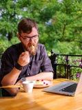 Lycklig ung man som arbetar på minnestavlan, medan sitta utomhus äganderätt för home tangent för affärsidé som guld- ner skyen ti Royaltyfria Bilder