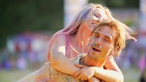Lycklig ung man som bär den härliga flickvännen på baksida, gladlynt krama för par lager videofilmer