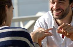 Lycklig ung man som föreslår förbindelse till kvinnan med förlovningsringen Royaltyfria Bilder