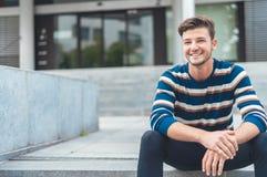 Lycklig ung man som framme sitter av tillträdesingången fotografering för bildbyråer