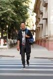 Lycklig ung man som g?r i gatan, ler och ser kameran som p? rymmer skuldror en ryggs?ck royaltyfri bild