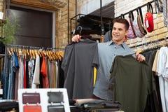 Lycklig ung man som gör shopping och innehavet två T-skjortor arkivfoto
