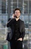 Lycklig ung man som går och talar på mobiltelefonen Arkivbild