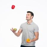 Lycklig ung man som jonglerar peppar Arkivfoton