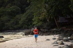 Lycklig ung man som kör på en strand på Ko Chang, Thailand i April, 2018 - bästa loppdestination för lycka royaltyfria foton