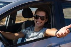 Lycklig ung man som k?r en hyrd bil i ?knen av Israel royaltyfri foto