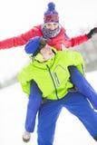 Lycklig ung man som på ryggen ger ritt till kvinnan i snö Arkivbild