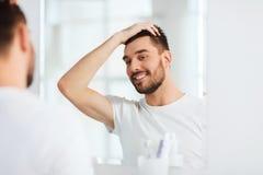 Lycklig ung man som ser för att avspegla det hemmastadda badrummet Royaltyfri Fotografi