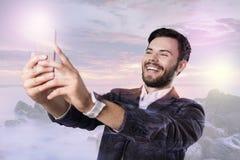 Lycklig ung man som ser upphetsad, medan ta foto royaltyfri bild