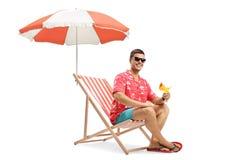 Lycklig ung man som sitter under paraplyet på en ferie och rymmer en coctail arkivbild