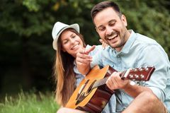Lycklig ung man som spelar gitarren till hans härliga flickvän royaltyfri bild