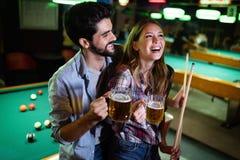 Lycklig ung man som spelar snooker med hans flickvän lyckligt ?lska f?r par royaltyfri bild