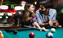 Lycklig ung man som spelar snooker med hans flickvän lyckligt ?lska f?r par arkivbild