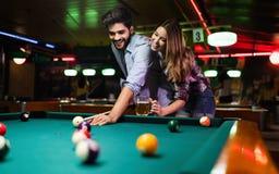 Lycklig ung man som spelar snooker med hans flickvän lyckligt ?lska f?r par arkivbilder