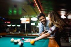 Lycklig ung man som spelar snooker med hans flickvän lyckligt ?lska f?r par royaltyfri fotografi