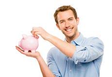 Lycklig ung man som sätter pengar i den isolerade spargrisen på vit Royaltyfri Foto