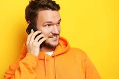 Lycklig ung man som talar på mobiltelefonen över gul bakgrund fotografering för bildbyråer