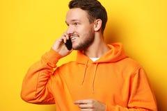 Lycklig ung man som talar på mobiltelefonen över gul bakgrund royaltyfri foto