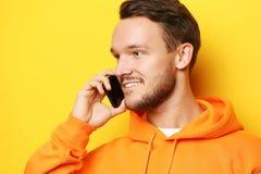 Lycklig ung man som talar på mobiltelefonen över gul bakgrund arkivbild