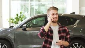 Lycklig ung man som talar på telefonen, når att ha köpt en ny bil på dealrrshipen arkivfilmer