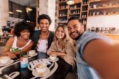 Lycklig ung man som tar selfie med vänner i ett kafé royaltyfri foto
